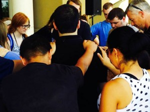 Team members pray with family and friends before their departure to fields of service.