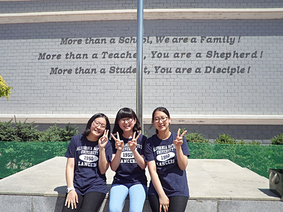 These three WanBang middle school students are part of the Skype pen pal program. The girls are sitting under a sign that publically proclaims the WanBang school motto.