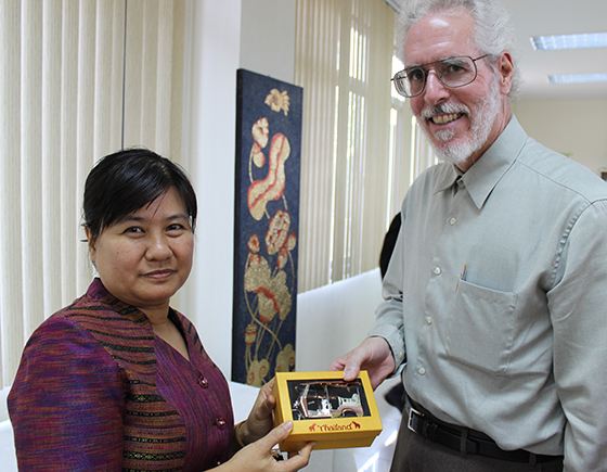 "The program director of English studies at the Siriwat Wittaya Bilingual School in Thailand presents Dr. Daniel Skubik with a model of a ""Tuk Tuk"" taxi, common in Bangkok."