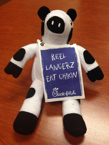 The Chick-fil-A stuffed cow will sport a Lancer placard for next week's grand opening.