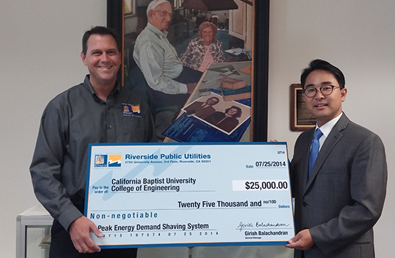 Ryan Gleason (left), RPU account manager, presents a grant check to Dr. Seunghyun Chu.
