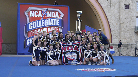 The Lancer cheer team poses with the NCA championship banner.