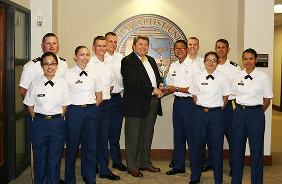 CBU Army ROTC presents the color guard trophy from the John J. Pershing Memorial Drill Competition to Dr. Ronald L. Ellis. From left: Cadet Jaymee Kwan, Sgt. 1st Class Jason Winkle, Cadet Shannon Garcia, Cadet Joel Powell, Cadet Caleb Fink, Dr. Ellis, Cadet Nathan Shimabukuro, Cadet Joshua Fink, Cadet Bryanna Mora, Cpt. William Brookshire, Cadet Sheraya Davis.