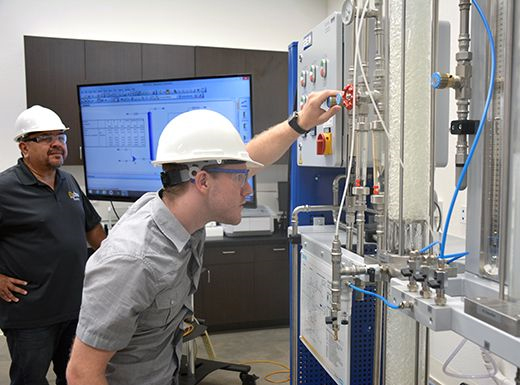 Stephen Dueck, chemical engineering student, works on calibrating a gas absorption unit used to remove CO2 from a gas stream.