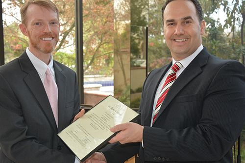 Dr. Daniel Prather (left), chair of CBU's aviation program, receives a Part 141 Air Agency Certification from Keith Frable, manager of the Federal Aviation Administration Riverside Flight Standard District Office.